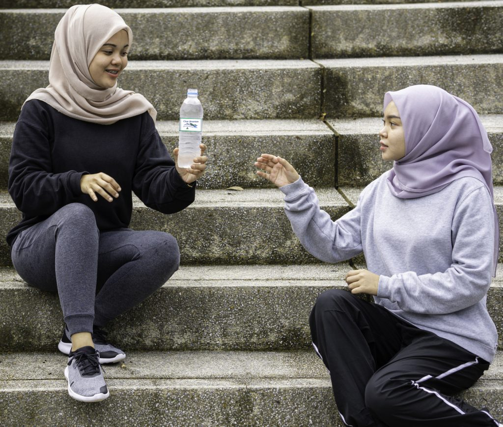 Beautiful muslim ladies sitting down and having a bottle of water at a public park during a sunny day after doing some exercise